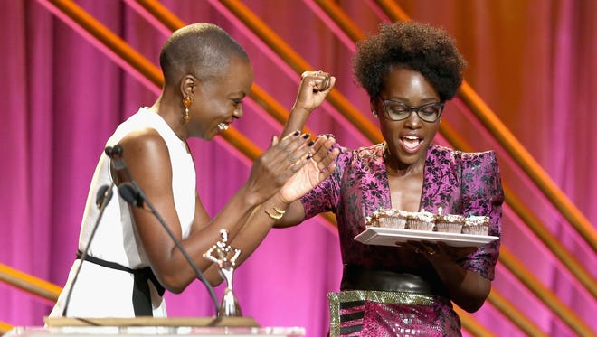 Danai Gurira surprises Lupita Nyong'o with a tray of birthday cupcakes during the 2018 Essence Black Women In Hollywood Oscars Luncheon on March 1.