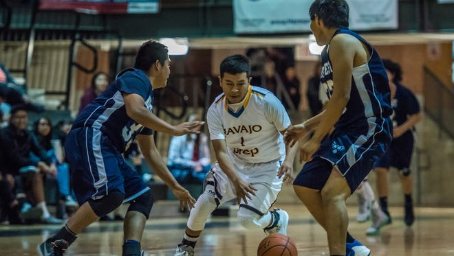 Navajo Prep's Tyler Morgan splits a pair of Shiprock Northwest defenders during a game on Thursday at the Eagles Nest in Farmington.