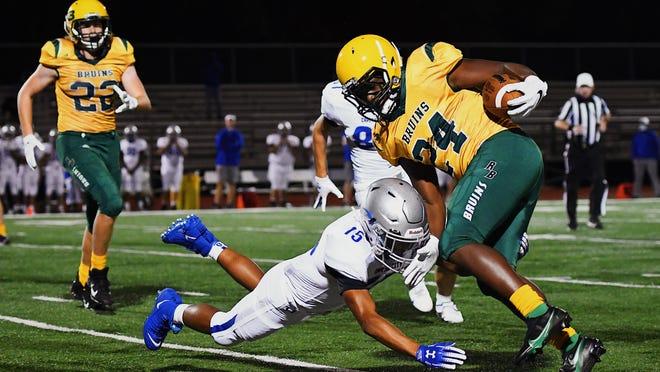Rock Bridge's Jonathan Garr (24) escapes the grip of Capital City's Isaiah Ntalamu (15) during a game Friday night at Rock Bridge High School.