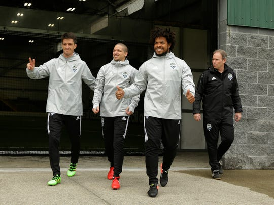 Sounders midfielders Alvaro Fernandez (left) and Osvaldo Alonso (center), walk with defender Roman Torres, second from right, and coach Brian Schmetzer (right) as they take the field for the first training session of the MLS season Tuesday in Tukwila.