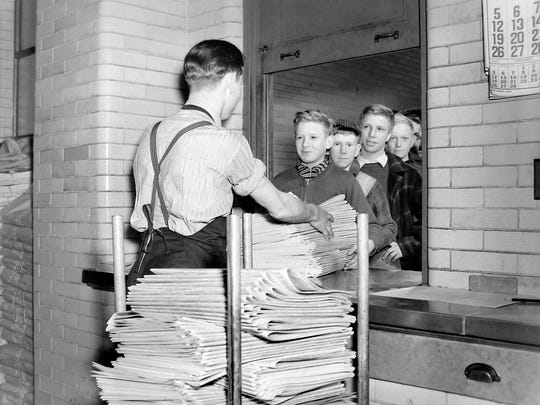 Newspaper carriers get their papers.