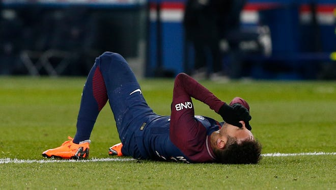 PSG's Neymar lays on the pitch after being fouled during the French League One soccer match between Paris Saint-Germain and Marseille at the Parc des Princes Stadium.