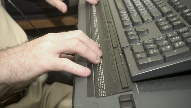 A worker uses speech and Braille aids on his workstation, an accommodation that gives him assistance in his job because of the Americans with Disabilities Act.