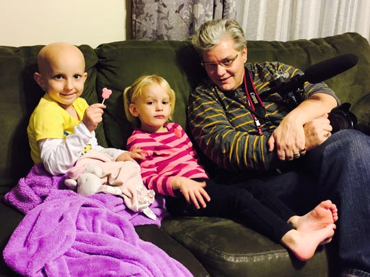 Democrat and Chronicle photographer Annette Lein sits on the couch with Amanda Conrow, left, and her little sister Emily at the Conrow's home in Rochester.