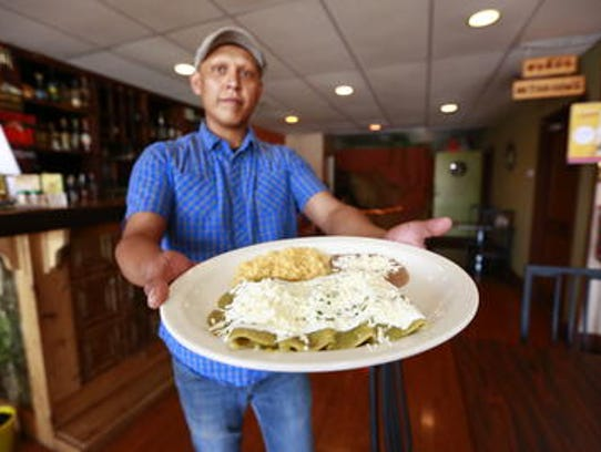 Edgar Carbajal holds out an enchilada dish his wife