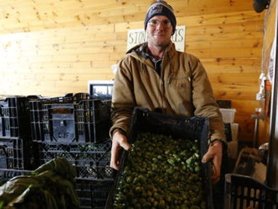 Tony Schultz holds up a tray of brussel sprouts Monday,