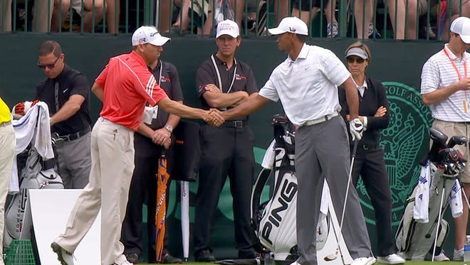 In this frame grab of a video image from Golf Channel, Sergio Garcia, left, shakes hands with Tiger Woods at the practice range Monday, June 10, 2013, in Ardmore, Pa., prior to this weekend's U.S. Open.