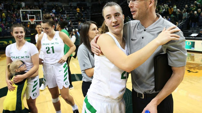Oregon's Sabrina Ionescu, center left, gets a hug from acting coach Mark Campbell, right, after the Ducks' win over Air Force on Dec. 20, 2018. Campbell was the acting coach with Kelly Graves sitting out the game as part of an NCAA suspension.