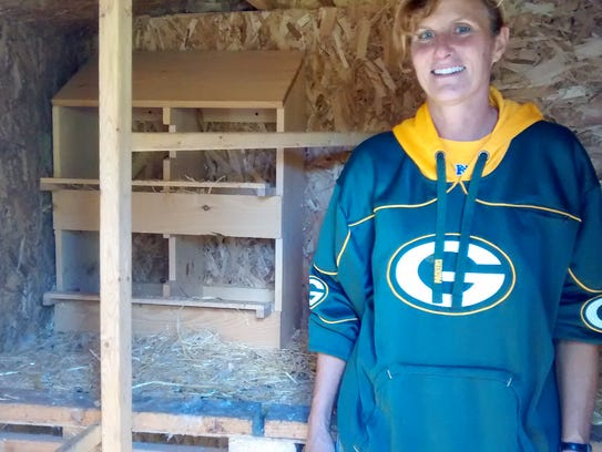 Susan Tubic stands beside the boxes where the chickens