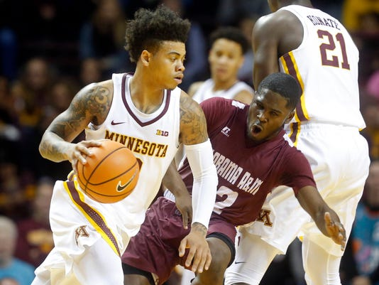 Minnesota's Nate Mason, left, drives around Alabama A&M's Terry Ellis Jr. in the first half of an NCAA college basketball game Tuesday, Nov. 21, 2017, in Minneapolis. (AP Photo/Jim Mone)