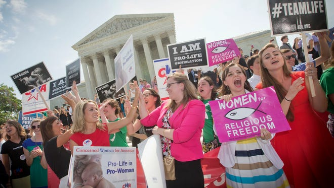 Demonstrators outside the Supreme Court on Monday hear the news that a 5-4 ruling has been issued in favor of Hobby Lobby.