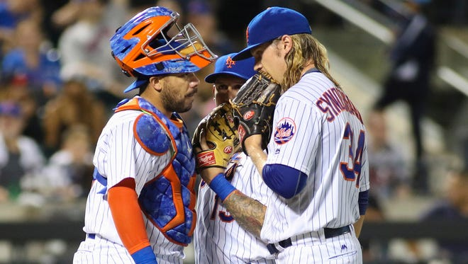 New York Mets pitcher Noah Syndergaard (34) talks to catcher Rene Rivera (44) and shortstop Asdrubal Cabrera (13) on the mound in the fourth inning against the Atlanta Braves at Citi Field on Monday.
