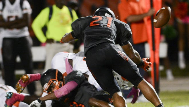 Cocoa's Javian Hawkins (3) and Zach Beagle (21) force a Jones fumble during Friday's game.