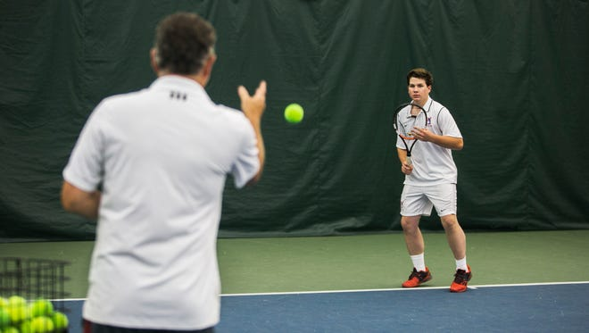 Edward Apple, 19, works on his forehand exercises with Tom Stem, left, a head pro at Leftwich Tennis Center on May 10, 2017. Apple was involved in a serious car accident on Aug. 6, 2015, that left him in a coma. The Memphis University School senior will soon attend Ole Miss in the fall.