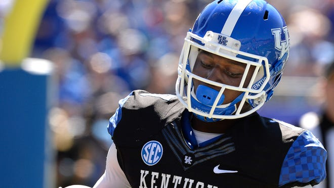 Kentucky's Alex Montgomery scores a touchdown on a 3-yard pass during the fourth quarter of an NCAA college football game against Louisville Saturday, Sept. 14, 2013, at Commonwealth Stadium in Lexington, Ky.