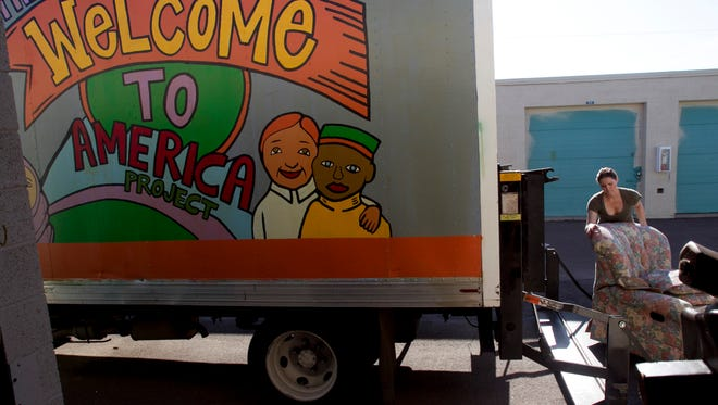 Megan O'Connor loads donated furniture into a Welcome to America Project truck for needy families in 2011.