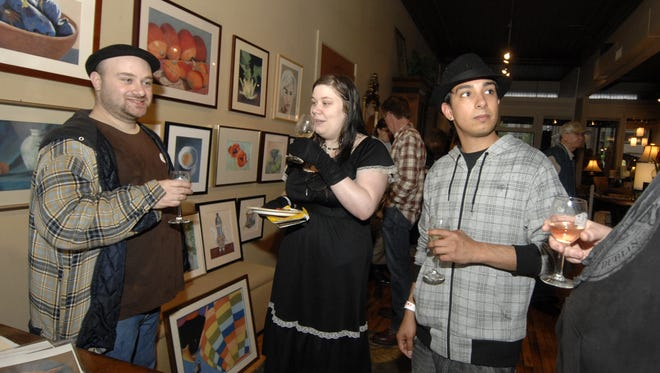 Spectators David Cohen, left, Katie Rowe, and Brian Betancourt sample some wines during the 2009 Exhibitour in downtown Wausau.