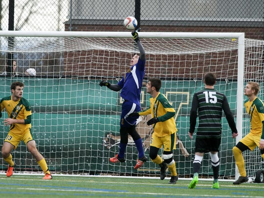 Vermont goalie Greg Walton (1) punches the ball away