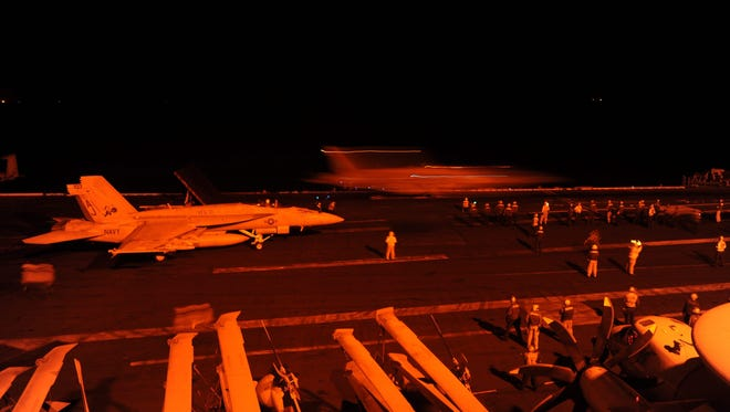 Two U.S. Navy F/A-18 Super Hornet jets prepare to launch from the flight deck of the aircraft carrier USS George H.W. Bush  to conduct strike missions against Islamic State targets in Syria on Tuesday.