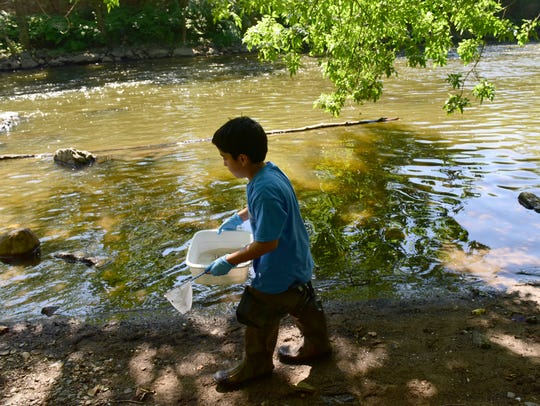 A students walks along the banks of the Passaic River