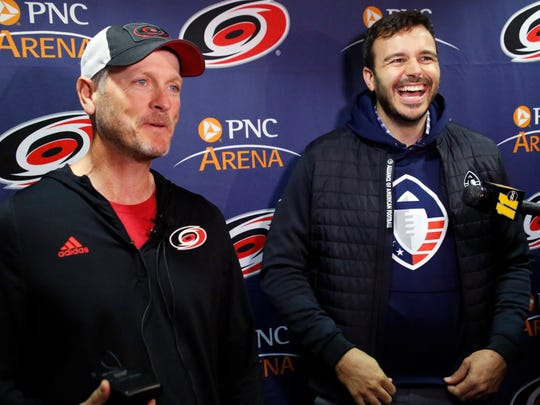 """FILE - In this Feb. 19, 2019, file photo, Tom Dundon, left, majority owner of the Carolina Hurricanes, and Charlie Ebersol, co-founder and CEO of the Alliance of American Football, talk to the media about Dundon's $250 million investment in the league, before an NHL hockey game between the New York Rangers and the Hurricanes in Raleigh, N.C. It's too early to tell what impact the Alliance of American Football will have on the sport itself. After all, this is its fourth weekend of games. Away from the field, with an infusion of backing from Dundon, the AAF is finding its footing. It's also finding what Ebersol calls """"substantial interest"""" in the league in such areas as sponsorships and partnerships, with three new partners signing on since the season opener three weeks ago. (AP Photo/Chris Seward, File) ORG XMIT: NY150"""
