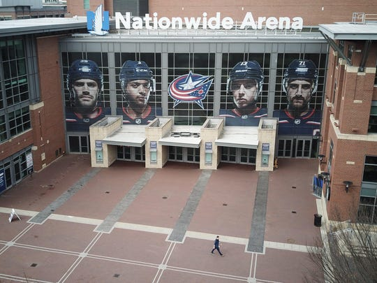 A person walks outside of Nationwide Arena on Thursday, March 12, 2020 in Columbus, Ohio. Earlier in the day, the NHL decided to suspend its season to aid in minimizing exposure and transmission of COVID-19 amid the coronavirus pandemic.