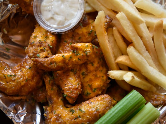 Some freshly-made chicken wings and fries are served