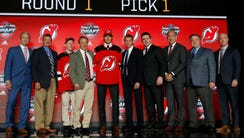 Center Nico Hischier holds a New Jersey Devils jersey