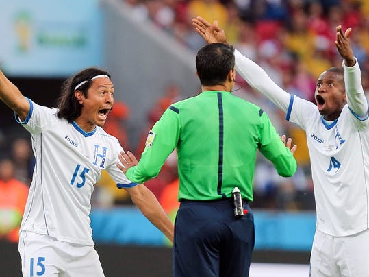 10ThingstoSeeSports - Honduras players  Roger Espinoza, left, and Luis Garrido complain to referee Sandro Ricci from Brazil after he awarded a goal to France using goal line technology during the group E World Cup soccer match between France and Honduras at the Estadio Beira-Rio in Porto Alegre, Brazil, Sunday, June 15, 2014. (AP Photo/David Vincent, File)