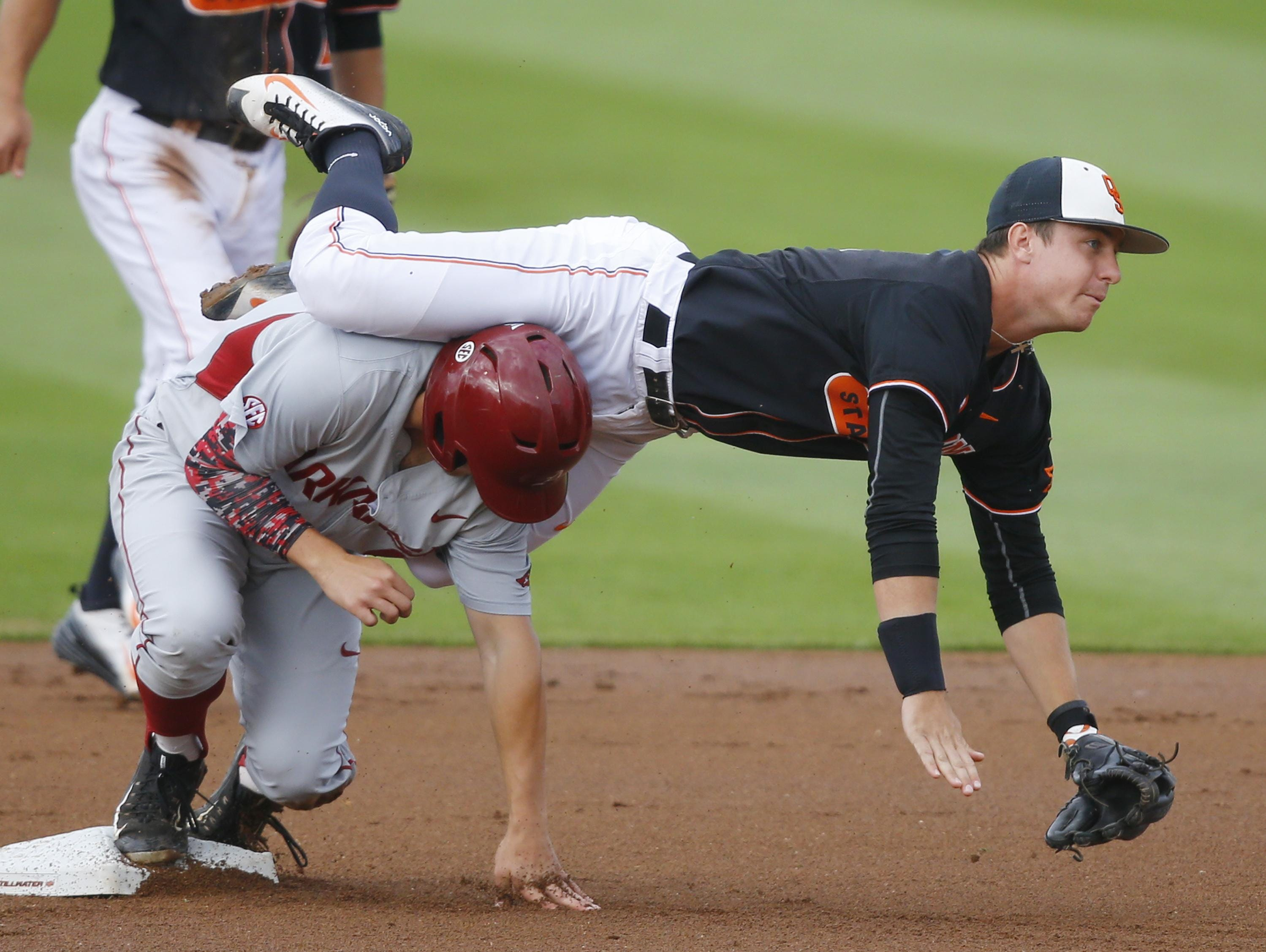 Oklahoma State shortstop Donnie Walton, top, tumbles over Arkansas' Joe Serrano while turning a double play during the Stillwater Regional on Saturday.