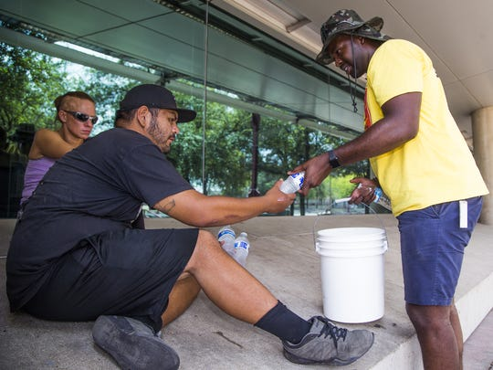 Jowan Thornton (right), of the Red Shield Survival Squad of the Salvation Army, hands water to Alex Jimenez near a Phoenix park. A mobile Salvation Army truck travels the streets of Phoenix with employees handing out water to those in need on days of unbearable heat.