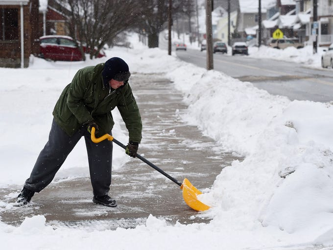 Connor Allessie, of Erie PA, shovels snow March 9,