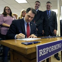 Governor Scott Walker signs Assembly Bill 373 Friday, Feb. 12, 2016, at Manpower Group in Appleton.