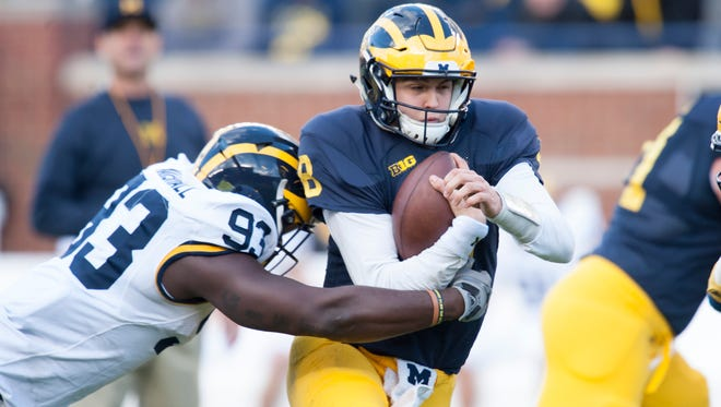 Michigan quarterback John O'Korn is tackled by defensive end Lawrence Marshall during Michigan's spring game.