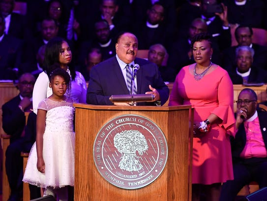Martin Luther King III speaks as he is flanked by his