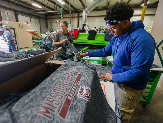 Calvin Lagrone, right, attaches tags to Missouri State