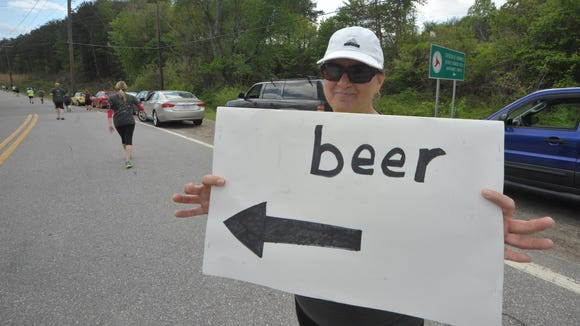 Anna Flowers holds a motivational direction sign at the inagural Run to the Taps at Highland Brewing.  The third race in the series is Saturday at Asheville Pizza and Brewing Co.