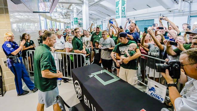 MSU Football Head Coach Mark Dantonio, left, is photographed by Spartan fans as he takes his seat to sign autographs during Meet the Spartans Tuesday at Spartan Stadium in East Lansing.