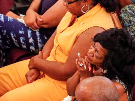 Denina Cupid Sharp, right, closes her eyes and listens to a prayer during a vigil Monday at Mount Olive Missionary Baptist Church for the nine members of the Coleman family who died in a duck boat accident in Branson, Missouri.