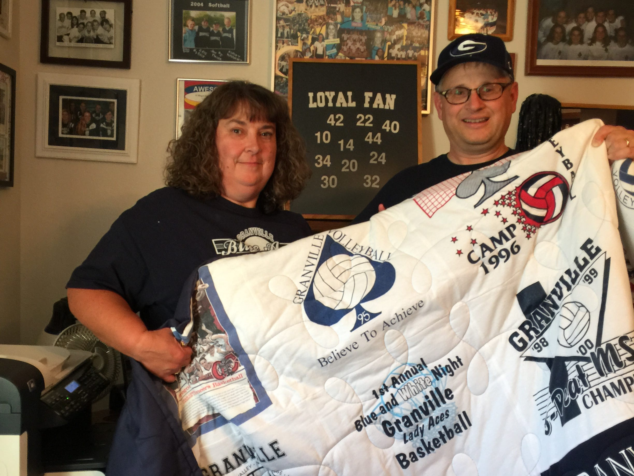 Sarah and Tim Davison display a quilt embroidered with various T-shirts from their 25 years of volunteering for Granville sports. Behind them, the walls in their home office are dominated by memorabilia given to them by the various teams.