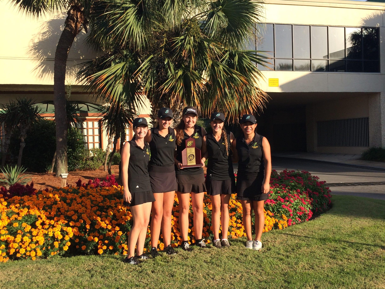 Catholic senior Abby Herrmann, center, holds region trophy with her teammates at Links Golf Club at Sandestin Resort.