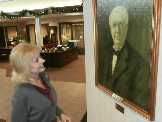 Edison National Bank President Robbie Roepstorff admires a painting provided by the Edison & Ford Winter Estates at the bank's location on U.S. 41 in south Fort Myers.