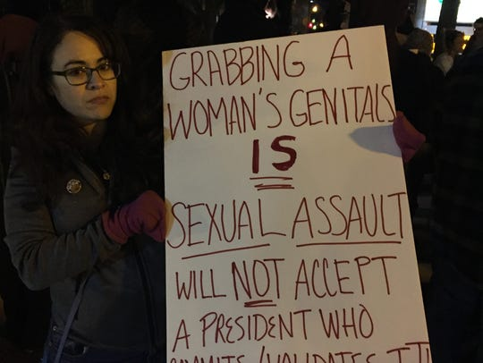 Mary Hippler holds sign at anti-Trump rally in Royal