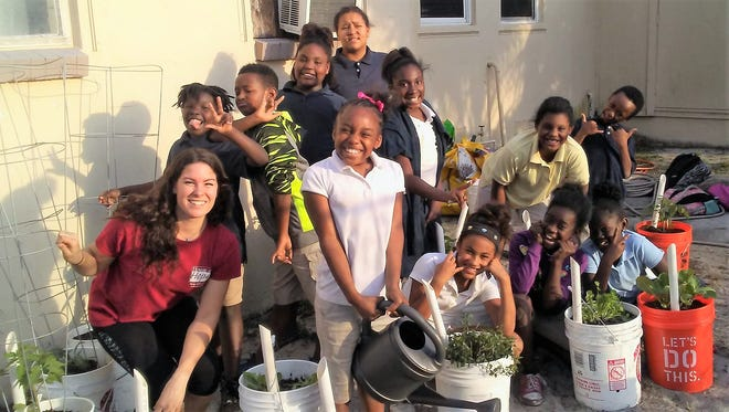 House of Hope agricultural coordinator Laura Lyman poses with Banner Lake Club students in their nutrition garden.