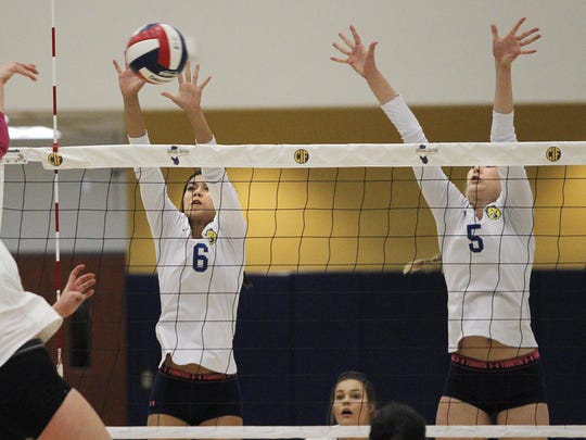 Exeter's Sydney Long and Madelyn Sweepe set up a block against Garces' Perri Starkey during a Central Section Division II championship volleyball game held in Lemoore, Calif., Saturday, Nov. 12, 2016 at West Hills College, Golden Eagle Arena.