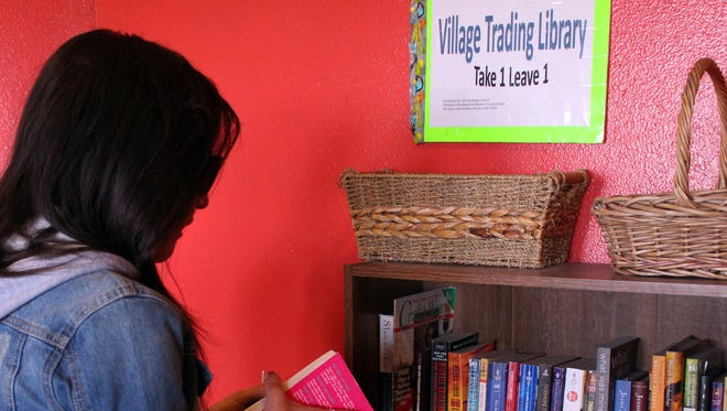 Abby Delira looks for a book to exchange in the Deming Literacy Program's community book shelf. at Peppers Supermarket.