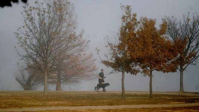 Tino Martinez and his dog, Rahkie, run through the morning fog on Saturday, Dec. 24, 2016, at Nelson Park.