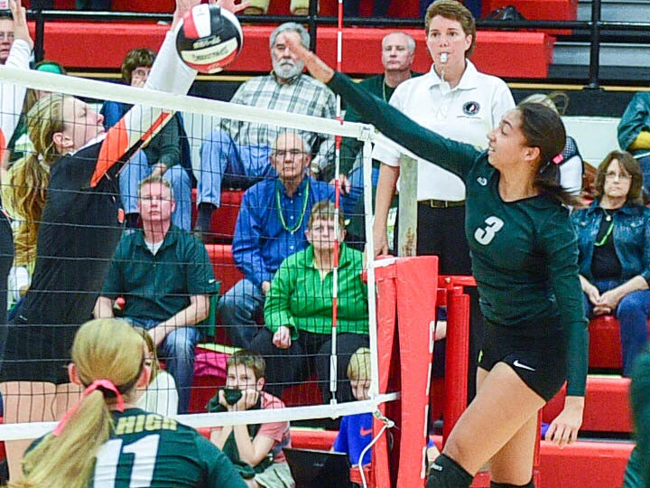 West High's Mikaela Mabry, right, spikes the ball but it is blocked by a Valley defender Tuesday in Newton.