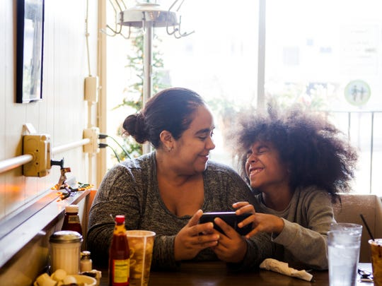 Renee and Kameron Laguna of Prospect Hill play a game together, while waiting for their breakfast at Tucker's Restaurant on Vine Street Wednesday, December 21, 2016. 
