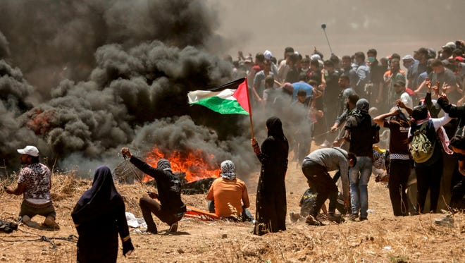 A Palestinian woman holds her national flag as Israeli forces and Palestinian protesters clash near the border between the Gaza Strip and Israel east of Gaza City on May 14, 2018.